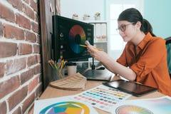 Χαμογελώντας θηλυκός σχεδιαστής που χρησιμοποιεί το κινητό τηλέφωνο κυττάρων Στοκ Εικόνα