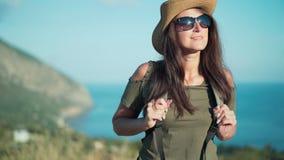 Χαμογελώντας θηλυκός ταξιδιώτης που έχει την οδοιπορία που συλλογίζεται το θαυμάσιο φυσικό τοπίο στο ηλιοβασίλεμα απόθεμα βίντεο