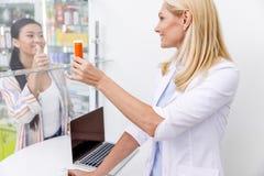 χαμογελώντας θηλυκός φαρμακοποιός που παρουσιάζει εμπορευματοκιβώτιο με το φάρμακο στην παρουσίαση πελατών στοκ φωτογραφία με δικαίωμα ελεύθερης χρήσης