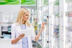 χαμογελώντας θηλυκός φαρμακοποιός στο άσπρο παλτό που κρατά την ψηφιακή ταμπλέτα στοκ εικόνα
