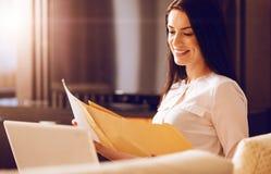 Χαμογελώντας θηλυκό που ελέγχει τα σημαντικά έγγραφα Στοκ φωτογραφίες με δικαίωμα ελεύθερης χρήσης