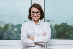 Χαμογελώντας ιατρικός γιατρός γυναικών στο νοσοκομείο, πανοραμικό παράθυρο υποβάθρου στοκ εικόνες με δικαίωμα ελεύθερης χρήσης