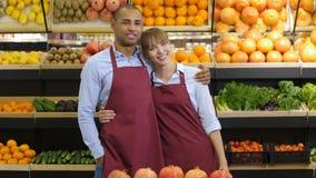 Χαμογελώντας ιδιοκτήτες που αγκαλιάζουν ενάντια στα ράφια στο κατάστημα φιλμ μικρού μήκους