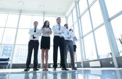 Χαμογελώντας και βέβαια επιχειρησιακή ομάδα που στέκεται μπροστά από έναν φωτεινό Στοκ Εικόνες