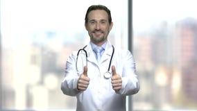 Χαμογελώντας καυκάσιος γιατρός που δίνει δύο αντίχειρες επάνω απόθεμα βίντεο