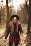 Χαμογελώντας καφετής-μαλλιαρή γυναίκα με το καπέλο στο δάσος απεικόνιση αποθεμάτων