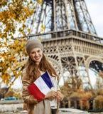Χαμογελώντας κομψή γυναίκα στο ανάχωμα στο Παρίσι, Γαλλία με τη σημαία Στοκ φωτογραφία με δικαίωμα ελεύθερης χρήσης