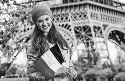 Χαμογελώντας κομψή γυναίκα στο ανάχωμα στο Παρίσι, Γαλλία με τη σημαία Στοκ Φωτογραφίες