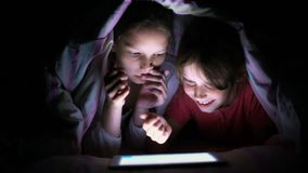 Χαμογελώντας κορίτσια που κάνουν σερφ την ταμπλέτα κάτω από το κάλυμμα τη νύχτα απόθεμα βίντεο