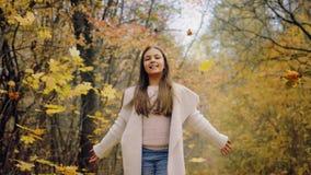 Χαμογελώντας κορίτσι εφήβων και ρίψη επάνω στο δάσος φθινοπώρου απόθεμα βίντεο