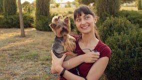Χαμογελώντας κορίτσι και μικρό τεριέ του Γιορκσάιρ σκυλιών που θέτουν υπαίθρια απόθεμα βίντεο