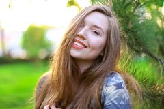 Χαμογελώντας κορίτσι κοντά στο ξύλο κέδρων με το πράσινο υπόβαθρο χλόης Στοκ εικόνες με δικαίωμα ελεύθερης χρήσης