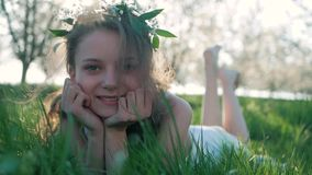 Χαμογελώντας κορίτσι ομορφιάς που βρίσκεται στο λιβάδι ανοίξεων με τα άγρια λουλούδια ευτυχές γέλιο απολαύστε τη φύση όμορφες νεο φιλμ μικρού μήκους