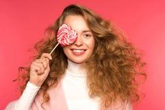 χαμογελώντας κορίτσι που καλύπτει το μάτι με την καρδιά που διαμορφώνεται lollipop Στοκ Εικόνες