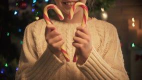 Χαμογελώντας κορίτσι που παρουσιάζει καραμέλες Χριστουγέννων στη κάμερα, ευτυχής μαγικός χρόνος διακοπών, κινηματογράφηση σε πρώτ απόθεμα βίντεο