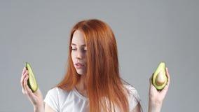 Χαμογελώντας κορίτσι που παρουσιάζει σε ένα μικρό αβοκάντο υγιή φρούτα απόθεμα βίντεο