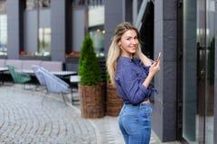 Χαμογελώντας κορίτσι που περπατά και που κρατά το smartphone στην πόλη Στοκ Φωτογραφία