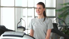 Χαμογελώντας κορίτσι που τρέχει treadmill απόθεμα βίντεο