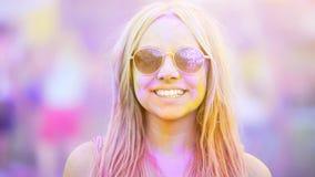Χαμογελώντας κορίτσι στα γυαλιά ηλίου που καλύπτονται στις ζωηρόχρωμες χρωστικές ουσίες, θερινές διακοπές, νεολαία Στοκ Φωτογραφίες