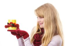 Χαμογελώντας κορίτσι στα μάλλινα γάντια που κρατά το διακοσμημένο φλυτζάνι του τσαγιού, διακόσμηση φθινοπώρου Στοκ Εικόνα