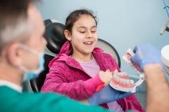 Χαμογελώντας κορίτσι στην καρέκλα οδοντιάτρων που εκπαιδεύει για το κατάλληλο δόντι-βούρτσισμα από τον παιδιατρικό οδοντίατρό της Στοκ φωτογραφία με δικαίωμα ελεύθερης χρήσης