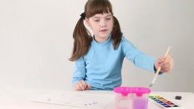 Χαμογελώντας κορίτσι στην μπλε πεταλούδα χρωμάτων watercolor στον πίνακα στο άσπρο δωμάτιο φιλμ μικρού μήκους