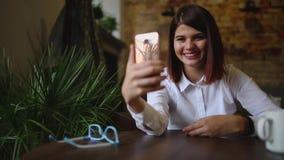 Χαμογελώντας κορίτσι στον καφέ που μιλά στην τηλεοπτική συνομιλία στο έξυπνο τηλέφωνο πίνοντας τον καφέ φιλμ μικρού μήκους