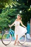 Χαμογελώντας κορίτσι στο άσπρο φόρεμα και τα υψηλά τακούνια που θέτουν κοντά στο μπλε ποδήλατο στο πάρκο στοκ εικόνες με δικαίωμα ελεύθερης χρήσης