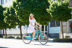 Χαμογελώντας κορίτσι στο άσπρο φόρεμα που οδηγά το μπλε εκλεκτής ποιότητας ποδήλατο και που κοιτάζει στη κάμερα στοκ εικόνες με δικαίωμα ελεύθερης χρήσης