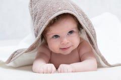Χαμογελώντας κοριτσάκι μετά από το ντους με την πετσέτα στο κεφάλι Ευτυχές γελώντας μωρό που φορά τη με κουκούλα πετσέτα που βρίσ στοκ εικόνα