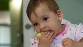 Χαμογελώντας κοριτσάκι που τρώει τη φέτα μήλων από μόνη της απόθεμα βίντεο