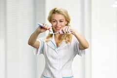 Χαμογελώντας κυρία που εφαρμόζει την οδοντόπαστα στην οδοντόβουρτσα Στοκ Φωτογραφία