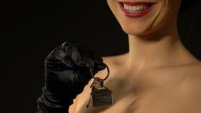 Χαμογελώντας κυρία που παρουσιάζει κλειδιά με το σπίτι keychain στη κάμερα, κτηματομεσιτική αγορά φιλμ μικρού μήκους