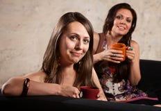 Χαμογελώντας κυρίες στον καναπέ με τις κούπες Στοκ εικόνα με δικαίωμα ελεύθερης χρήσης