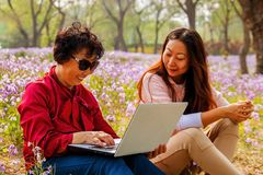 Χαμογελώντας κόρη που παρουσιάζει φορητό προσωπικό υπολογιστή στη μητέρα καθμένος σε ένα πάρκο στοκ φωτογραφίες με δικαίωμα ελεύθερης χρήσης