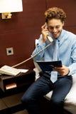 Χαμογελώντας κύριος που τοποθετεί μια κατάταξη πέρα από το τηλέφωνο Στοκ φωτογραφία με δικαίωμα ελεύθερης χρήσης