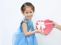 Χαμογελώντας λίγο κορίτσι παιδιών που λαμβάνει το κόκκινο κιβώτιο δώρων καρδιών που απομονώνεται στο άσπρο υπόβαθρο Ημέρα του βαλ στοκ εικόνα