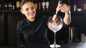 Χαμογελώντας λατρευτό θηλυκό bartender που βάζει τη φράουλα σε ένα γυαλί με το συντριμμένο πάγο προετοιμάζοντας το κοκτέιλ Νυχτερ απόθεμα βίντεο