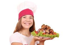 Χαμογελώντας μάγειρας κοριτσιών με τα κεφτή στο πιάτο στοκ φωτογραφίες
