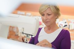 Χαμογελώντας μέση ηλικίας γυναίκα που χρησιμοποιεί τη ράβοντας μηχανή στο πλυντήριο Στοκ εικόνα με δικαίωμα ελεύθερης χρήσης