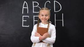 Χαμογελώντας μαθήτρια που αγκαλιάζει το βιβλίο, αλφάβητο που γράφεται στον πίνακα πίσω, σύστημα απόθεμα βίντεο