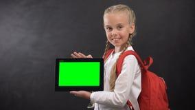 Χαμογελώντας μαθήτρια που παρουσιάζει ταμπλέτα με την πράσινη οθόνη στη κάμερα, εκπαιδευτικό app απόθεμα βίντεο