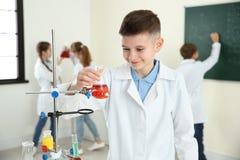 Χαμογελώντας μαθητής που εξετάζει τη φιάλη με το αντιδραστήριο στην κατηγορία στοκ εικόνες