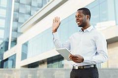 Χαμογελώντας μαύρος επιχειρηματίας με την ταμπλέτα που χαμογελά και που κάνει τη χειρονομία υποδοχής Στοκ Εικόνες