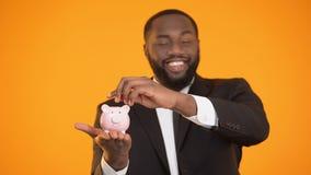 Χαμογελώντας μαύρος στο κοστούμι που βάζει το νόμισμα στο piggybank, οικονομική βασική εκπαίδευση, αποταμίευση απόθεμα βίντεο