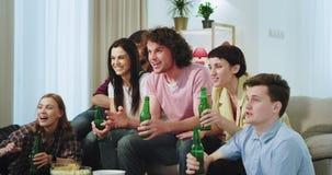 Χαμογελώντας μεγάλοι πολύ χαρισματικοί φίλοι που προσέχουν έναν αγώνα ποδοσφαίρου μαζί στον καναπέ υποστηρίζουν την ομάδα τους εν φιλμ μικρού μήκους