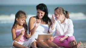Χαμογελώντας μητέρα και κόρες που χρησιμοποιούν την ταμπλέτα στην παραλία φιλμ μικρού μήκους
