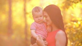 Χαμογελώντας μητέρα με το μωρό στο ηλιοβασίλεμα απόθεμα βίντεο
