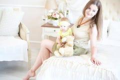 Χαμογελώντας μητέρα που αγκαλιάζει το μικρό κορίτσι της στο κρεβάτι Στοκ εικόνα με δικαίωμα ελεύθερης χρήσης