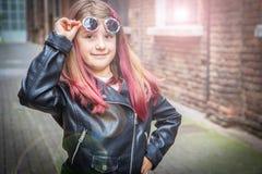Χαμογελώντας μικρό κορίτσι με τα γυαλιά ηλίου και το σακάκι δέρματος στοκ εικόνες
